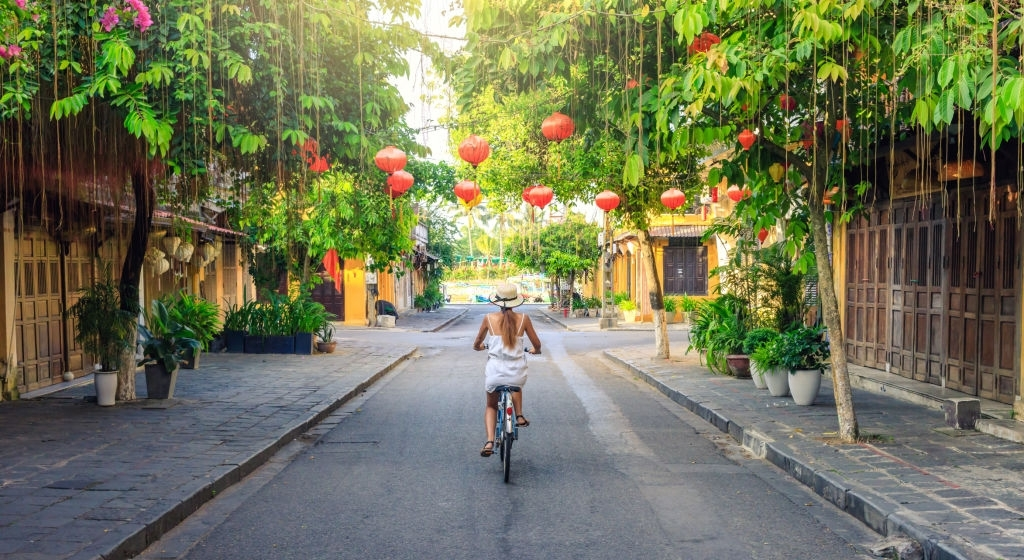 women-visiting-the-old-city-of-hoi-an-in-vietnam-by-bike-during-morning